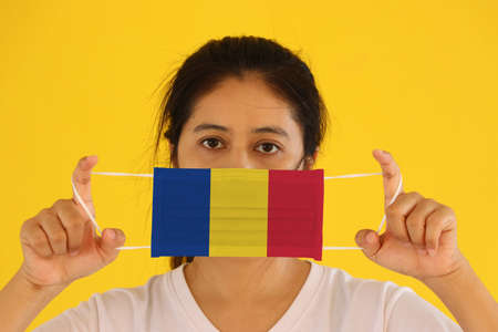 A woman in white shirt with Romania flag on hygienic mask in her hand and lifted up the front face on yellow background. Tiny Particle or virus corona or Covid 19 protection. Concept of Combating illness. Reklamní fotografie