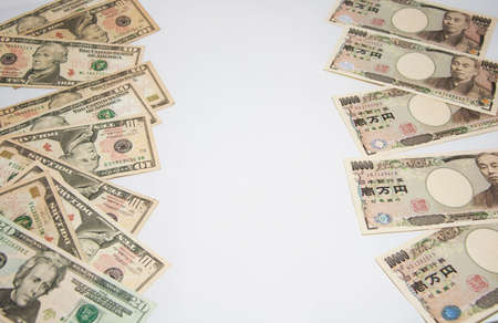 Exchange money concept, The pile of US banknotes on the left and The pile of Japanese banknotes on right with white background.