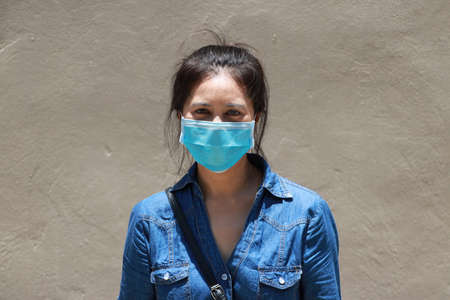 Masked Asian woman prevent germs and wear denim skirt dress. Tiny Particle or Covid 19 protection. Concept of Combating illness.