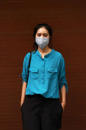 Masked Asian woman prevent germs and wear blue shirt. Tiny Particle or virus corona or Covid 19 protection. Concept of Combating illness.