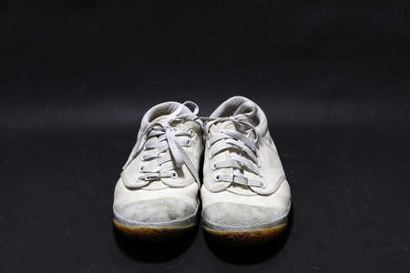 Used sneakers shoes in white color but it grimy and Gloomy color, put pair on black floor. it is a soft shoe with a rubber sole worn for sports or casual occasions. 版權商用圖片
