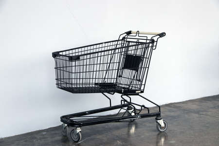 Black shopping Cart on the floor and white background. trolley is a cart supplied by a shop, especially supermarkets, for use by customers for transport to checkout counter during shopping. Stock Photo