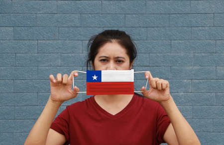 A woman and hygienic mask with Chile flag pattern in her hand and raises it to cover her face. A mask is a very good protection from Tiny Particle or virus corona or Covid 19. Reklamní fotografie