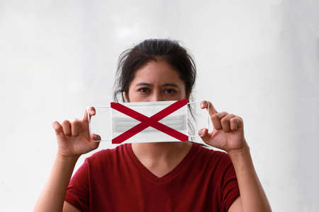 A woman and hygienic mask with Alabama flag pattern in her hand and raises it to cover her face. A mask is a very good protection from Tiny Particle or virus corona or Covid 19.