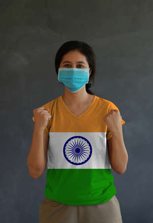 Masked woman wearing India flag color of shirt and standing with raised both fist on dark wall background. Concept of protection and fighting COVID.