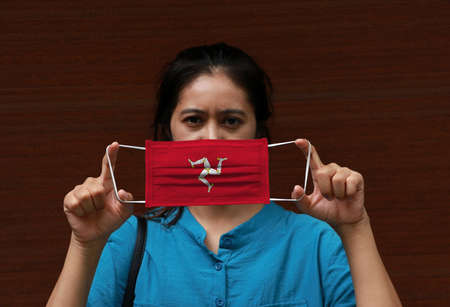 A woman and hygienic mask with Isle of man flag pattern in her hand and raises it to cover her face on dark background. A mask is a very good protection from Tiny Particle or virus corona or Covid 19.