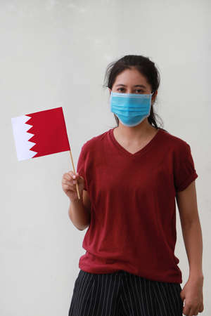 Masked woman in brown shirt and Bahrain flag in hand. Concept of protection and fighting COVID.