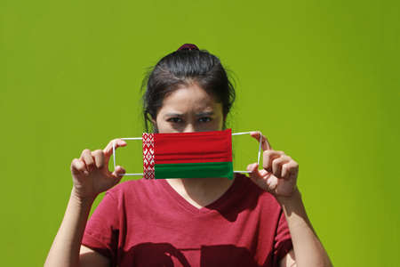 A woman and hygienic mask with Belarus flag pattern in her hand and raises it to cover her face on green background. A mask is a very good protection from Tiny Particle or virus corona.