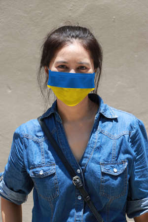 Ukraine flag on hygienic mask. Masked woman prevent germs and wear denim dress. Tiny Particle or virus corona protection. Concept of Combating illness.