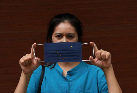 A woman and hygienic mask with Alaska flag pattern in her hand and raises it to cover her face on dark brown background. A mask is a very good protection from Tiny Particle or virus corona or Covid 19.