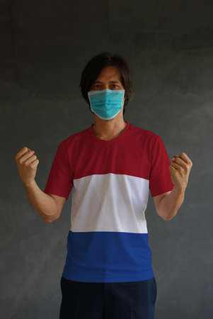 Man wearing hygienic mask and wearing Netherlands flag colored shirt and standing with raised both fist on dark wall background. Concept of protect tiny dust or disease.