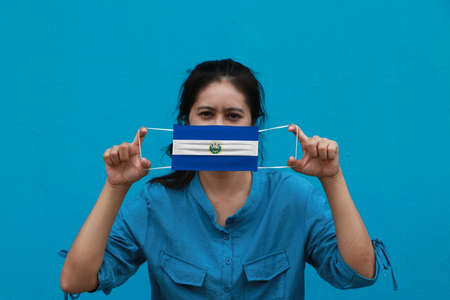 A woman and hygienic mask with El Salvador flag pattern in her hand and raises it to cover her face on blue background. A mask is a very good protection from Tiny Particle or virus corona or Covid 19.