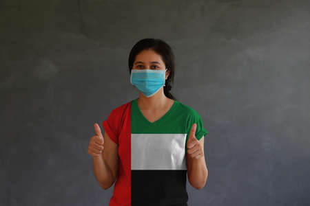 Woman wearing hygienic mask and wearing UAE flag colored shirt with thumbs up with both hands on dark wall background. Concept of protect tiny dust or disease. Archivio Fotografico
