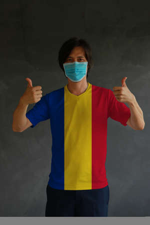 Man wearing hygienic mask and wearing Romanian flag colored shirt with thumbs up on both hands. Concept of protect tiny dust or disease of Romania. Archivio Fotografico