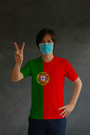 Man wearing hygienic mask and wearing Portuguese flag colored shirt and raising two fingers up on dark wall background. Concept of protect tiny dust or disease of Portugal.