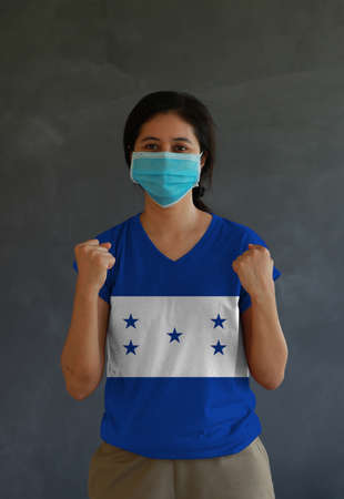 Woman wearing hygienic mask and wearing Honduras flag colored shirt and standing with raised both fist on dark wall background. Concept of protect tiny dust or disease.