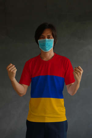 Man wearing hygienic mask and wearing Armenia flag colored shirt and standing with raised both fist on dark wall background. Concept of protect tiny dust or disease.