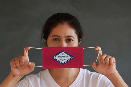 A woman and hygienic mask with Arkansas flag pattern in her hand and raises it to cover her face. A mask is a very good protection from Tiny Particle or virus corona or Covid 19.