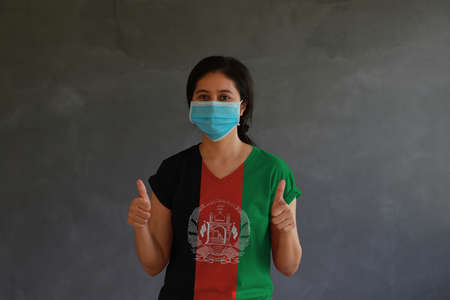 Woman wearing hygienic mask and wearing Afghanistan flag colored shirt with thumbs up with both hands on dark wall background. Concept of protect tiny dust or disease.