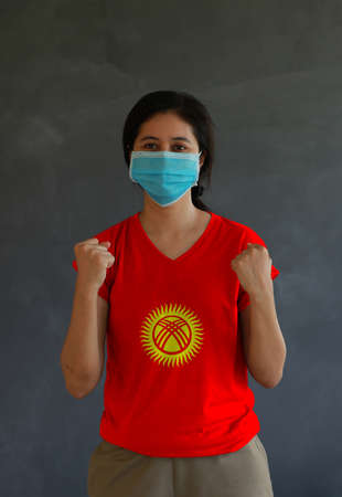 Woman wearing hygienic mask and wearing Kyrgyzstan flag colored shirt and standing with raised both fist on dark wall background. Concept of protect tiny dust or disease.