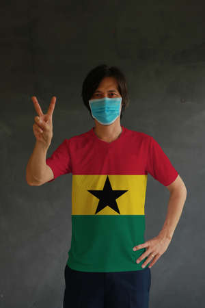 Man wearing hygienic mask and wearing Ghanaian flag colored shirt and raising two fingers up on dark wall background. Concept of protect tiny dust or disease of Ghana. Archivio Fotografico
