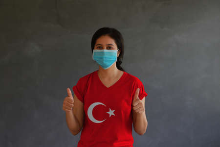 Woman wearing hygienic mask and wearing Turkey flag colored shirt with thumbs up with both hands on dark wall background. Concept of protect tiny dust or disease.