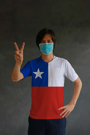 Masked man wearing Chile flag color of shirt and raising two fingers up on dark wall background. Concept of protection and fighting COVID. Archivio Fotografico