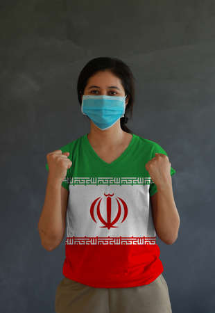 Masked woman wearing Iran flag color of shirt and standing with raised both fist on dark wall background. Concept of protection and fighting COVID 19.