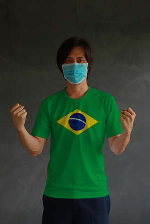 Masked man wearing Brazil flag color of shirt and standing with raised both fist on dark wall background. Concept of protection and fighting COVID. Archivio Fotografico