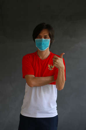 Man wearing hygienic mask and wearing Indonesian flag colored shirt and cross one s arm with thumbs up on dark wall background. Concept of protect tiny dust or disease of Indonesia.