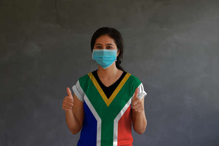 Masked woman wearing South Africa flag color of shirt and thumbs up with both hands on dark wall background. Concept of protection and fighting COVID. Archivio Fotografico