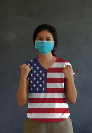 Masked woman wearing USA flag color of shirt and standing with raised both fist on dark wall background. Concept of protection and fighting COVID. Archivio Fotografico