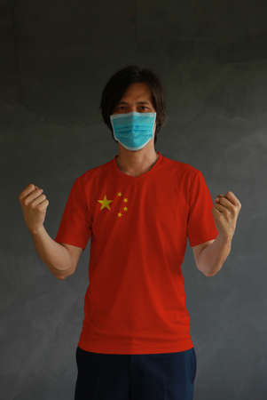 Man wearing hygienic mask and wearing China flag colored shirt and standing with raised both fist on dark wall background. Concept of protect tiny dust or disease.