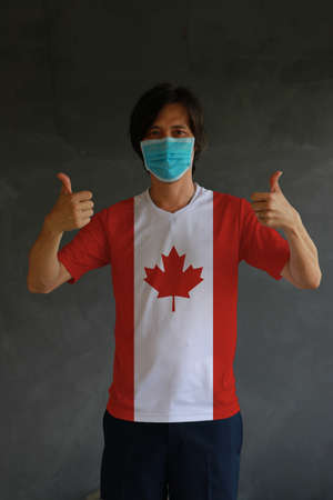 Man wearing hygienic mask and wearing Canadian flag colored shirt with thumbs up on both hands. Concept of protect tiny dust or disease of Canada.