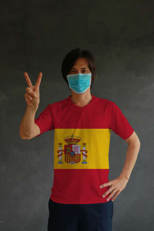 Masked man wearing Spain flag color of shirt and raising two fingers up on dark wall background. Concept of protection and fighting COVID.