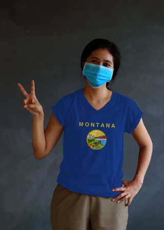 Woman wearing hygienic mask and wearing Montana flag colored shirt, Spanish for Gold and silver, and raising two fingers up on dark wall background. Concept of protect tiny dust or disease.
