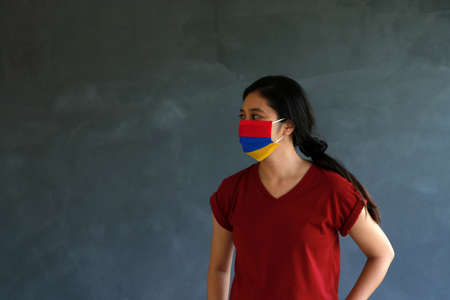 Woman wearing Armenian flag colored hygienic mask with brown shirt and facing to the side on dark wall background. Concept of protect tiny dust or disease of Armenia.
