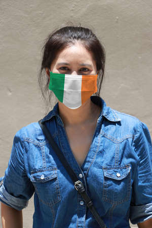 Ireland flag colored on hygienic mask. Masked woman prevent germs and wear denim dress. Tiny Particle or virus corona protection. Concept of Combating illness.