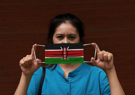 A woman and hygienic mask with Kenya flag pattern in her hand and raises it to cover her face on dark brown background. A mask is a very good protection from Tiny Particle or virus corona.