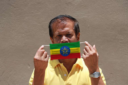 A man and hygienic mask with Ethiopia flag pattern in his hand and raises it to cover his face on brown background. A mask is a very good protection from Tiny Particle or virus corona.