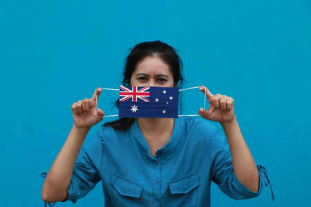 A woman and hygienic mask with Australia flag pattern in her hand and raises it to cover her face on blue background. A mask is a very good protection from Tiny Particle or virus corona.
