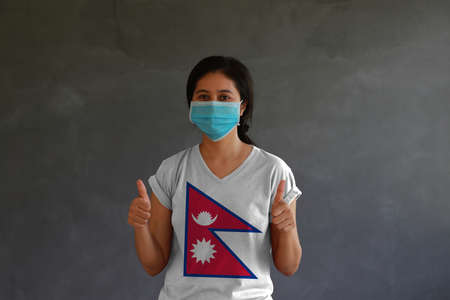 Woman wearing hygienic mask and wearing Nepal flag colored shirt with thumbs up with both hands on dark wall background. Concept of protect tiny dust or disease. Archivio Fotografico