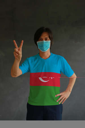 Man wearing hygienic mask and wearing Azerbaijani flag colored shirt and raising two fingers up on dark wall background. Concept of protect tiny dust or disease of Azerbaijan.