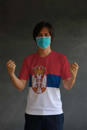 Man wearing hygienic mask and wearing Serbia flag colored shirt and standing with raised both fist on dark wall background. Concept of protect tiny dust or disease.