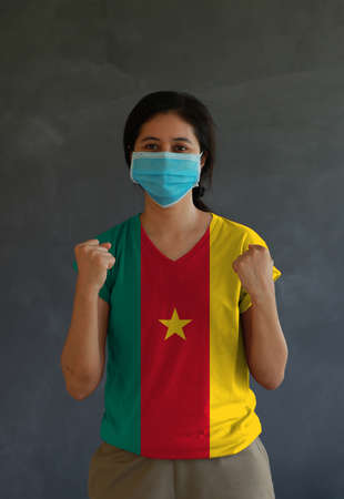 Woman wearing hygienic mask and wearing Cameroon flag colored shirt and standing with raised both fist on dark wall background. Concept of protect tiny dust or disease.