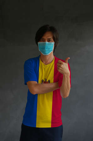 Man wearing hygienic mask and wearing Moldovian flag colored shirt and cross one s arm with thumbs up on dark wall background. Concept of protect tiny dust or disease of Moldova.