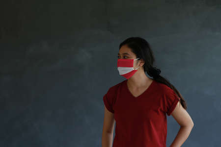 Woman wearing Austrian flag colored hygienic mask with brown shirt and facing to the side on dark wall background. Concept of protect tiny dust or disease of Austria.