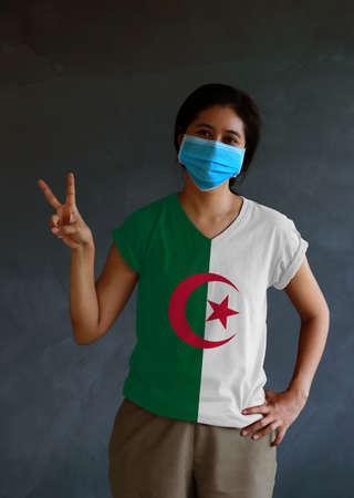 Woman wearing hygienic mask and wearing Algerian flag colored shirt and raising two fingers up on dark wall background. Concept of protect tiny dust or disease of Algeria.