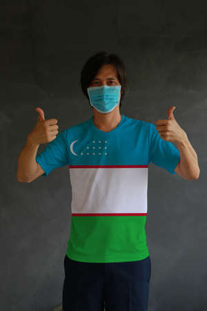 Man wearing hygienic mask and wearing Uzbek flag colored shirt with thumbs up on both hands. Concept of protect tiny dust or disease of Uzbekistan. Reklamní fotografie