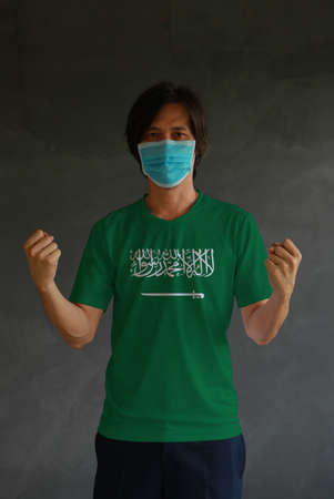 Masked man wearing Saudi Arabia flag color of shirt and standing with raised both fist on dark wall background. Concept of protection and fighting COVID 19. Archivio Fotografico